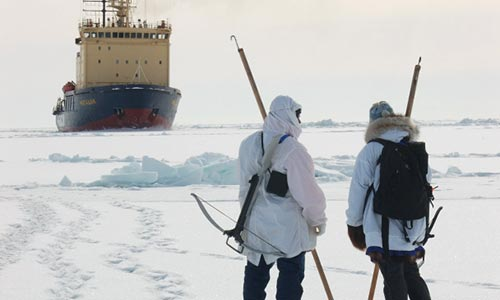 Two people on the ice holding testing sticks with a ship in the background