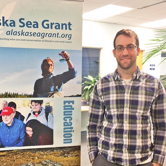 Richard Buzard standing with a Sea Grant banner