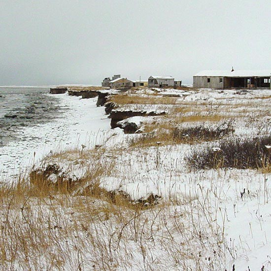 winter coastline with buildings near the edge of eroding cliffs