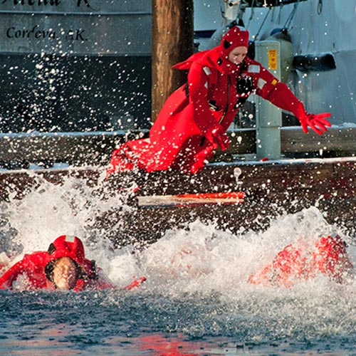 people in survival suits jumping into the water