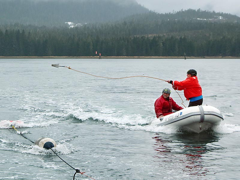 two people in small boat on the water, one tossing a grappling hook