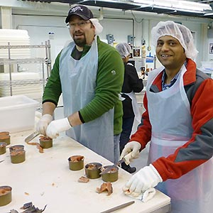 two people canning salmon